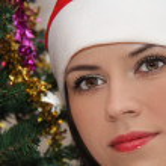 Young beauty smiling santa woman near the Christmas tree — Stock Photo #52444197