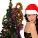 Young beauty smiling santa woman near the Christmas tree — Stock Photo #52444209