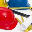 Colorful helmets and tools for construction drawings and buildin — Stock Photo #67181315