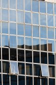 Glass facade with opened windows — Stock Photo