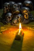 Skulls with candle burning on wooden background in the darkness  — Stock Photo