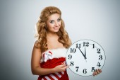 Smiling christmas woman with clock — Stock Photo