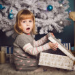 Little girl surprised with big present near the christmas tree — Foto Stock #58366805