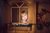 Meisje in houten huis met decoratie van Kerstmis — Stockfoto