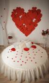 Romantic interior with round bed and hearts on the wall — Stock Photo