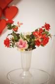Romantický interiér - váza s červenými růžemi — Stock fotografie