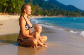 A young mother with a child having fun on a tropical beach.. Nat — Foto Stock