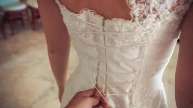 The bridesmaid helps to lace up corset wedding dress of the bride. — Stock Video
