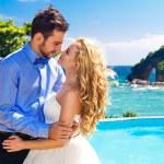 Happy bride and groom having fun on a tropical beach — Stock Photo #62194385