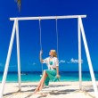 Young beautiful girl sitting on a swing under a palm tree. Blue — Stock Photo #62294547