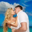 Happy bride and groom kissing on a tropical beach. Blue sea in t — Photo #62296115