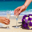 Wedding bouquet and two glasses of champagne on the sand. Male a — Stock Photo #62296859