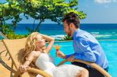 Happy bride and groom enjoy a cocktail poolside infinity. Tropic — Stock Photo