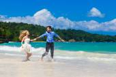 Happy bride and groom having fun on a tropical beach — Stock Photo