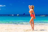 Ung vacker flicka i bikini stående på stranden. Blå tr — Stockfoto