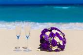 Wedding bouquet and two glasses of champagne on the sand. Blue s — Stock Photo