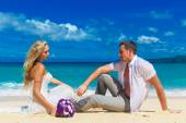 Bride and groom on a tropical beach. wedding bouquet in the fore — Stock Photo