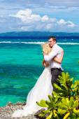 Happy bride and groom having fun on a tropical beach under the p — Stock Photo