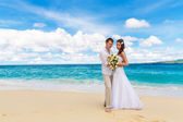 Happy bride and groom having fun on a tropical beach — Stock Photo