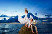 Bride and groom on a tropical beach with the sunset in the backg — Stock Photo