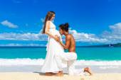 Happy and young pregnant couple having fun on a tropical beach.  — Zdjęcie stockowe