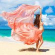 Young pregnant woman with pink cloth fluttering in the wind on a — Stock Photo #63791713