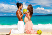 Happy and young pregnant couple with coconuts having fun on a tr — Stock Photo
