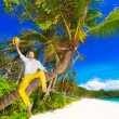 Happy man in yellow trousers and white shirt sitting on a palm t — Stock Photo #73778507