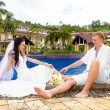 Happy groom and bride sitting by the pool. Wedding and honeymoon — Stock Photo #73771693