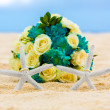 Two wedding rings with two starfish and wedding bouquet on a sandy tropical beach. Wedding and honeymoon in the tropics. — Stock Photo #73774803