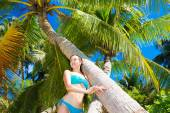 Beautiful young woman in blue bikini relaxes under palm trees. — Stock Photo