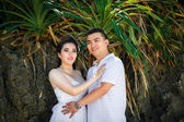 Asian bride and groom on a tropical beach. Wedding and honeymoo — Stock Photo