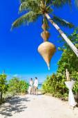 счастливые новобрачные, весело проводящие время на тропическом пляже под p — Стоковое фото