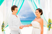 Groom giving an engagement ring to his bride under the arch deco — Stock Photo