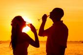 Silhouette of couple enjoying glass of champagne on tropical bea — Stock Photo
