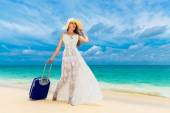 Beautiful young woman in white dress and straw hat with a suitca — Stock Photo