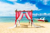 Wedding ceremony on a tropical beach in red. Arch decorated with — Stock Photo