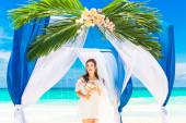 Wedding ceremony on a tropical beach in blue. Happy bride under — Stock Photo