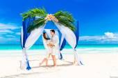 Cerimônia de casamento numa praia tropical em azul. Br e noivo feliz — Fotografia Stock