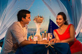 Young beautiful couple have a romantic dinner at sunset on a tro — Stock Photo