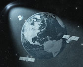 Earth and orbiting satellites drawing  in spot of light  — Stock Photo