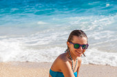 Young woman in sunglasses at beach — Stock Photo