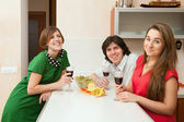 Three young people drink wine — Stock Photo
