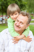 Grandfather and grand son in park — Stock Photo