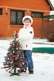 Smiling boy with Cristmas tree — Stock Photo