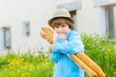 Boy with French baguettes — Stock Photo