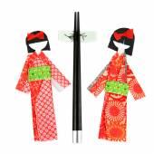 Japanese paper dolls and chopsticks — Stock Photo
