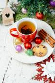 Christmas celebration tea time with cinnamon, cookie and baubles with Christmas tree background — Stock Photo