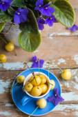 Blue tea cup full with yellow cherries with violets in a pot — Stock Photo