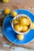 Blue tea cup full with yellow juicy cherries — Stockfoto